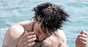 Man in pool shaking his wet hair